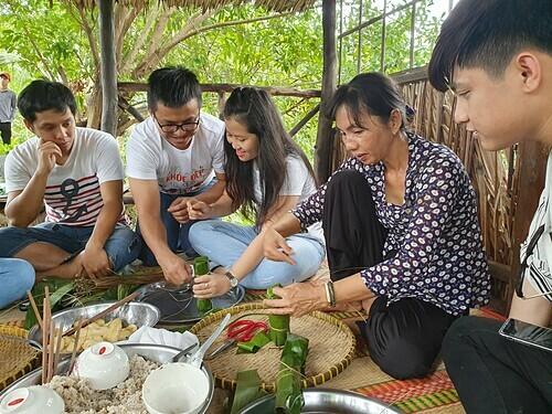 Du khách trải nghiệm hoạt động gói bánh tét ở khu du lịch cộng đồng Cồn Sơn, Cần Thơ.