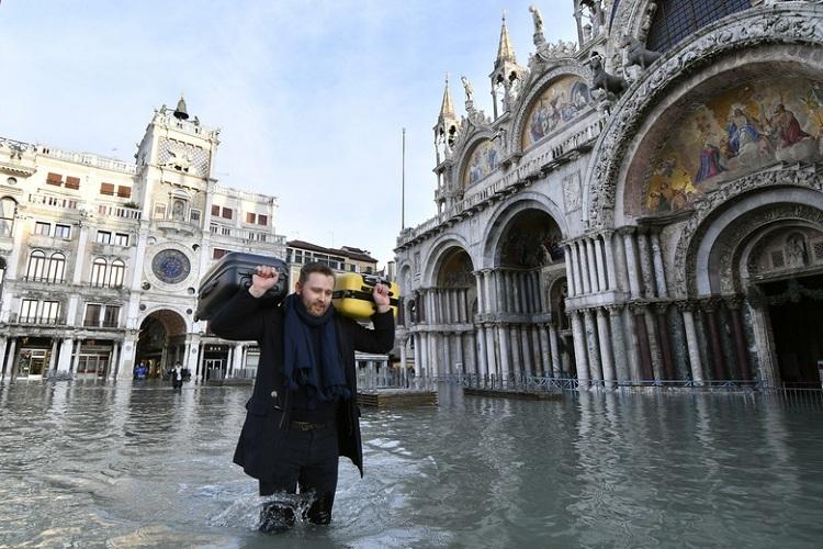 Một du khách vác hành lý trên vai khi lội nước trên quảng trường St. Mark tại Venice, Italy vào 23/12. Mực nước lúc này dâng cao khoảng 1,44 m. Ảnh: Luigi Costantini/AP.