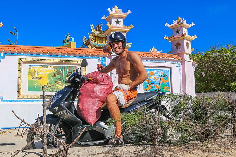 Vận động viên lướt sóng Nga Igor Yudakov tự lái xe máy để vận chuyển các bao rác. Ảnh: Maria Nelasova