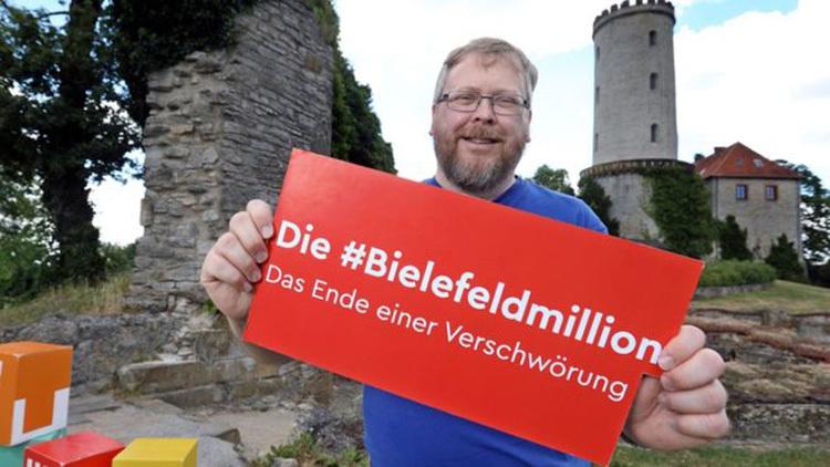Achim Held giơ biển ủng hộ cuộc thi Bielefeld không tồn tại. Ảnh: BBC.