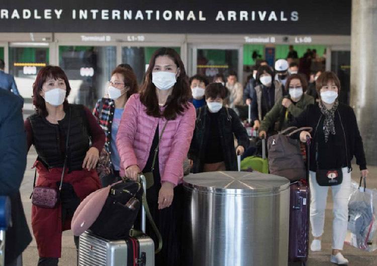 Các hành khách đeo khẩu trang để tự bảo vệ khi hạ cánh xuống sân bay Los Angeles, Mỹ. Ảnh: AFP.