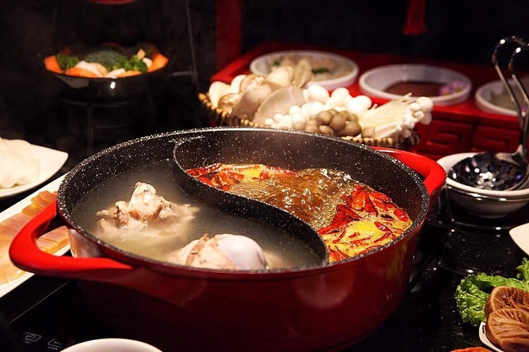 Món lẩu gồm một bên nước thịt hầm dinh dưỡng và một bên nước dùng kiểu Tứ Xuyên cay nồng. Ảnh: KAKHU.