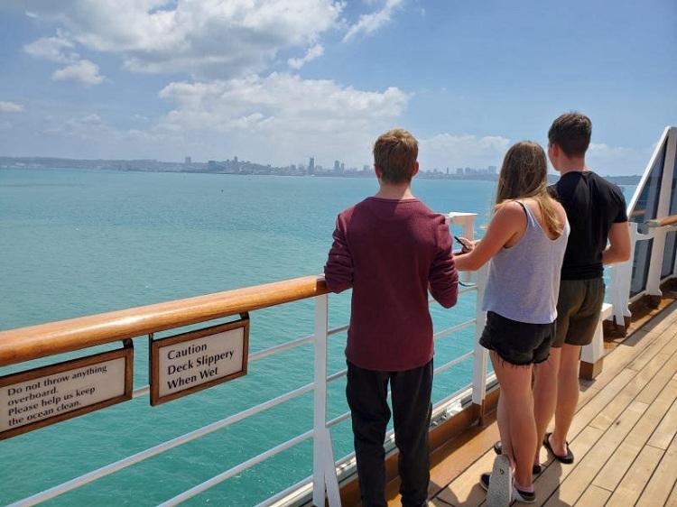 Hành khách trên tàu MS Westerdam nhìn về phía thị trấn cảng  Sihanoukville của Campuchia, nơi tàu được cấp phép cập cảng vào 13/2. Ảnh: Angela Jones/Reuters.