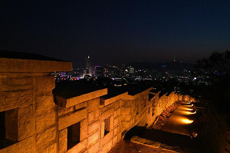 Pháo đài SeoulBan đêm, bạn có thể thực hiện một chuyến đi bộ dọc theo pháo đài Seoul. Con đường kéo dài từ cổng Hyehwamun đến cổng Heunginjimun, dọc theo đường cong của bức tường Pháo đài sẽ được thắp sáng. Khi đi bộ tại đây, bạn sẽ được nhìn ngắm những vì sao đêm ở Seoul cũng như toàn cảnh thành phố về đêm.