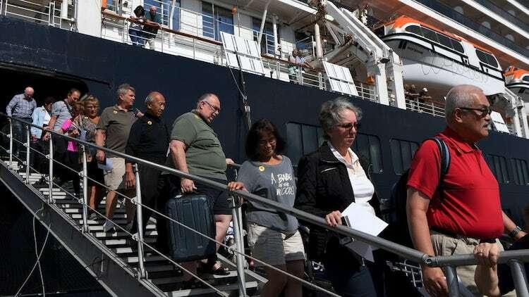 Hành khách rời tàu MS Westerdam sau khi hoàn thành thủ tục kiểm tra y tế. Ảnh: Tang Chhin Sothy/AFP.