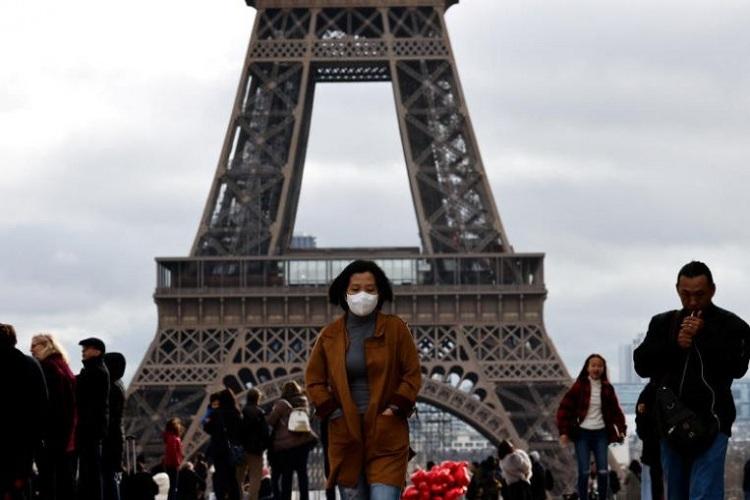 Một du khách đeo mặt nạ bảo vệ khi đi bộ phía trước tháp Eiffel, Paris vào 1/2, giữa mùa Covid-19 bùng phát. Ảnh: Reuters.