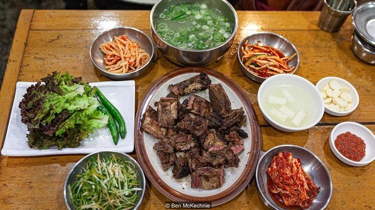 Thực khách ăn galbi có thể ăn kèm kimchi, rau diếp, ớt xanh và chấm sốt ớt. Ảnh: Ben Mckechnie.