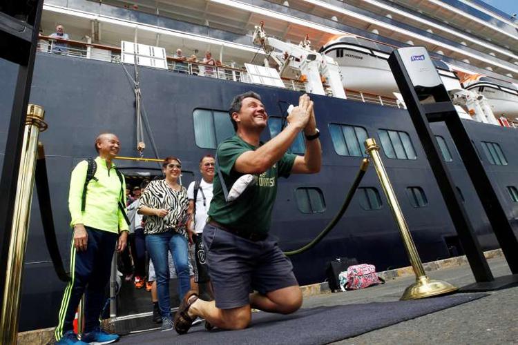 John Miller, du khách đến từ đảo Orcas, bang Washington, Mỹ đã khuỵu chân, chắp hai tay thể hiện sự biết ơn, vui mừng khi được rời tàu. Ảnh: AP.