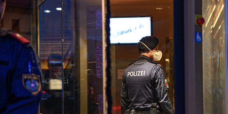 Một cảnh sát đeo khẩu trang trước khi vào trong khách sạn Grand Europa sau khi nơi này bị cách ly vì một nhân viên dương tính với nCoV. Ảnh: Reuters.