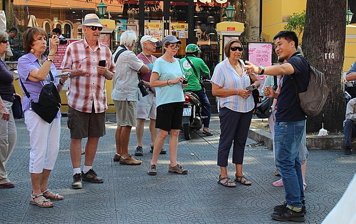 Đoàn du khách châu Âu đang nghe hướng dẫn viên thuyết minh ở phía trước Bưu điện TP HCM sáng ngày 21/2. Ảnh: Nguyễn Nam