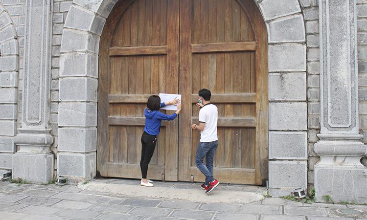 Nhân viên Khu di tích Cố đô Hoa Lư dán thông báo ngừng đón khách tham quan. Ảnh: Lam Sơn.