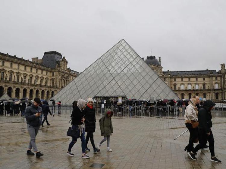Du khách xếp hàng dài đứng đợi dưới mưa, rồi lại quay về vì bảo tàng không mở cửa vào sáng 1/3. Ảnh: AFP.