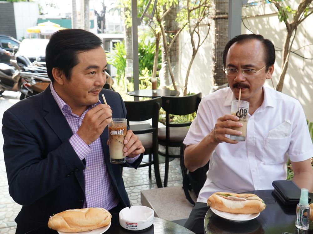 Ông Bùi Tá Hoàng Vũ (trái) và ôngông Võ Quốc Thắng - một trong ba thành viênsáng lập chuỗicà phêÔng Bầu (phải) - đang thưởng thức cà phê và bánh mì tại chi nhánh cà Phê Ông Bầu, sáng 24/3.