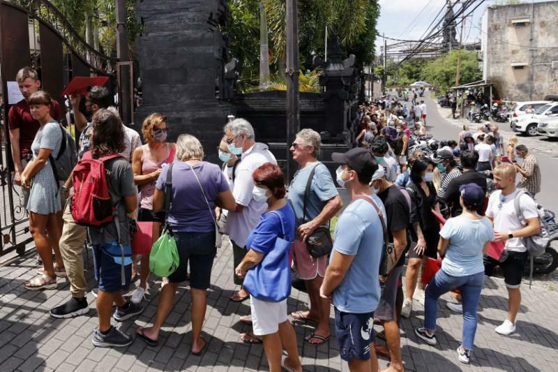 Người nước ngoài xếp hàng ngoài văn phòng quản lý xuất nhập cảnh ở Bali giữa Covid-19. Ảnh:Johannes P. Christo/Reuters.