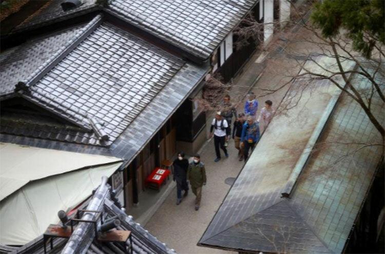Một nhóm nhỏ du khách đi dạo trong khu vực đền Kyiomizu-dera ở Kyoto hôm 15/3. Ảnh: Reuters.