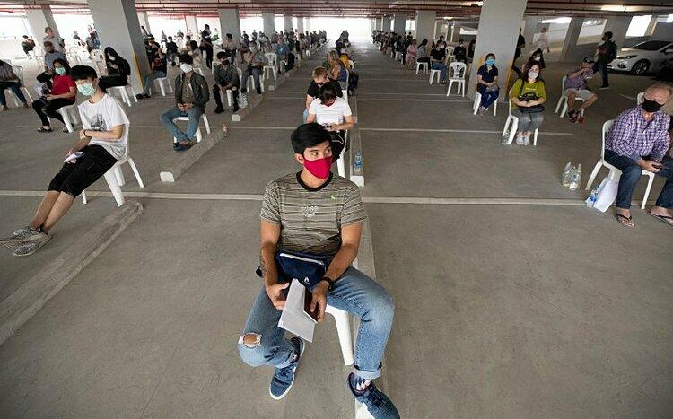 Du khách duy trì khoảng cách khi xếp hàng gia hạn thị thực tại Cơ quan quản lý xuất nhập cảnh Thái Lan ở Bangkok vào hôm 27/3. Ảnh:Sakchai Lalit/AP.