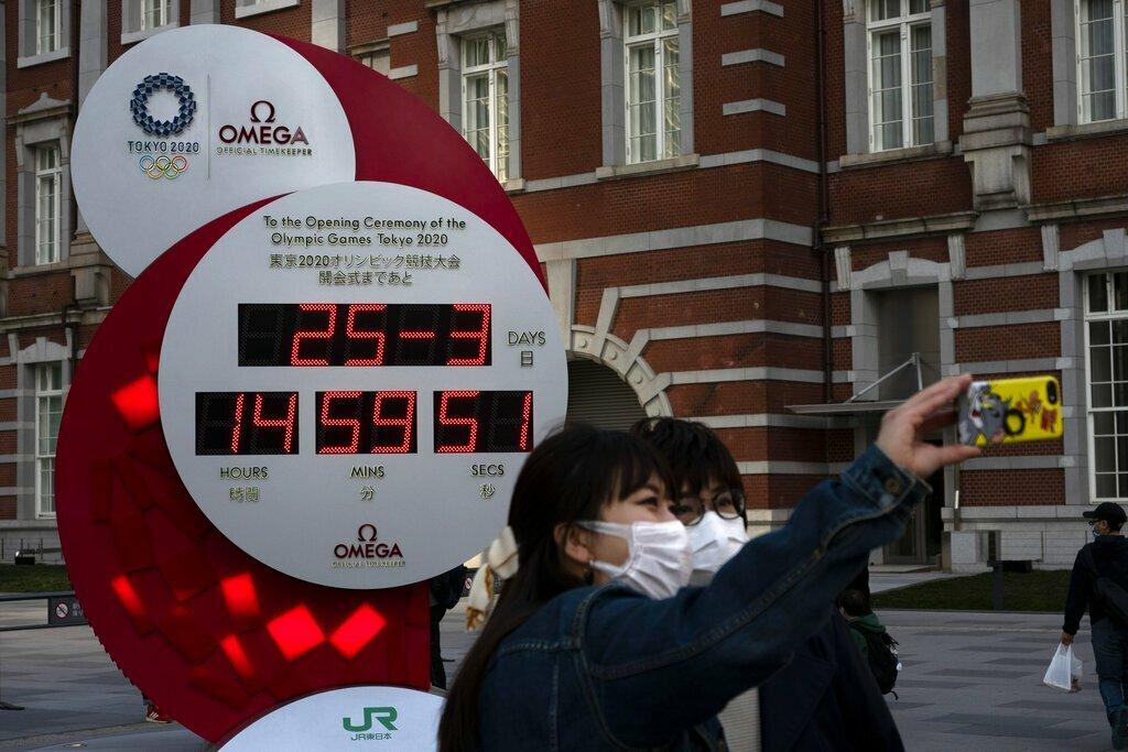 Người dân chụp ảnh với đồng hồ đếm ngược Olympic 2020, hiển thị ngày giờ hiện tại bên ngoài ga Tokyo. Đại dịch coronavirus đã buộc phải hoãn Thế vận hội. Ảnh: Jae C Hong / AP