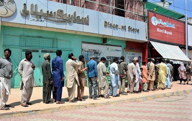 Người dân xếp hàng chờ nhận thức ăn từ thiện khi toàn quốc phong toả. Ảnh:M Saeed Qureshi/APP.