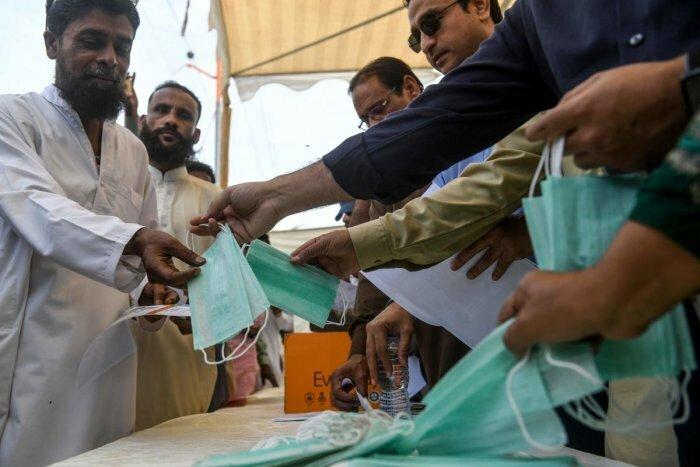 Giới chức Pakistan phát khẩu trang miễn phí và tờ rơi hướng dẫn phòng ngừa nCoV cho người dân trên đường phố Karachi vào tháng 3. Ảnh:AFP.