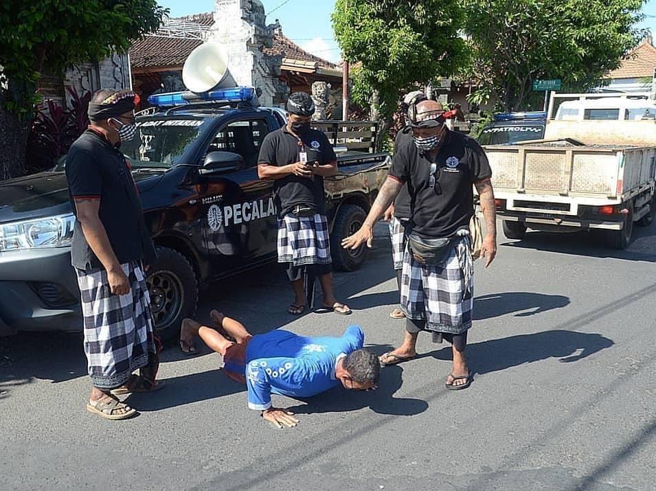 Pecalang, lực lượng an ninh địa phương, phạt người không đeo khẩu trang khi ra đường. Ảnh:Denpasar Now.