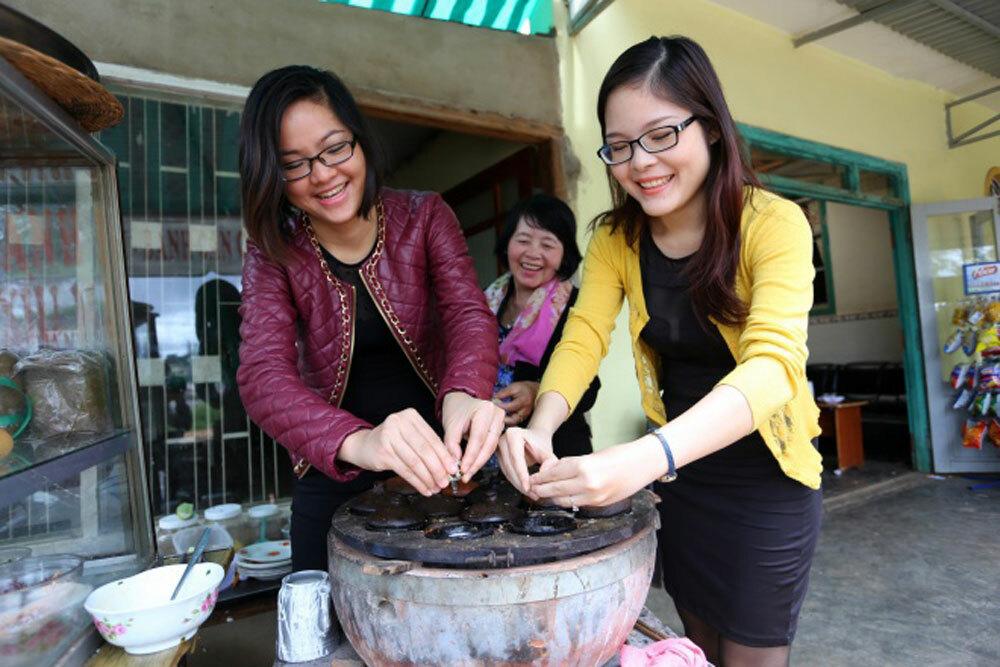 Helen (trái) học làm bánh căn tại cửa hàng bánh căn ở Đà Lạt. Ảnh: NVCC.