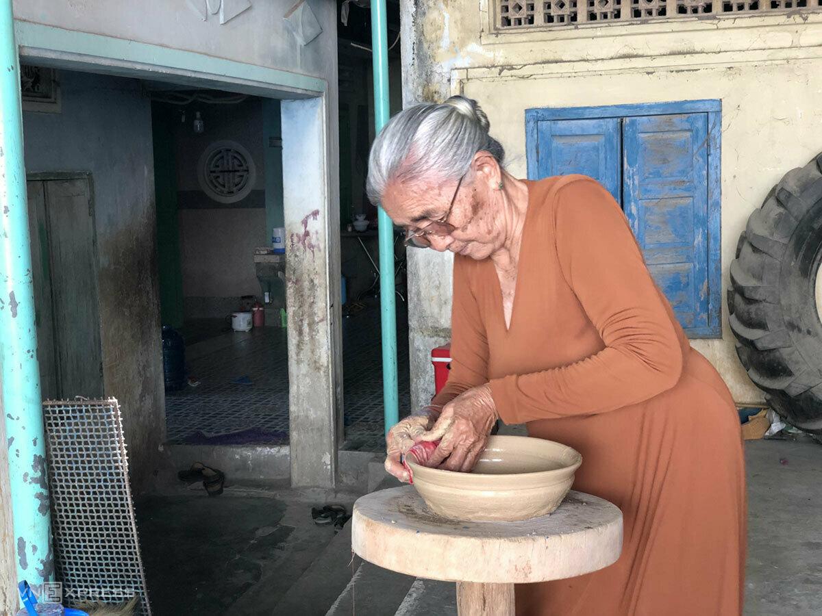 Nghệ nhân Đơn Thị Hiệu mô tả quá trình làm gốm Chăm. Ảnh: Ngân Dương.