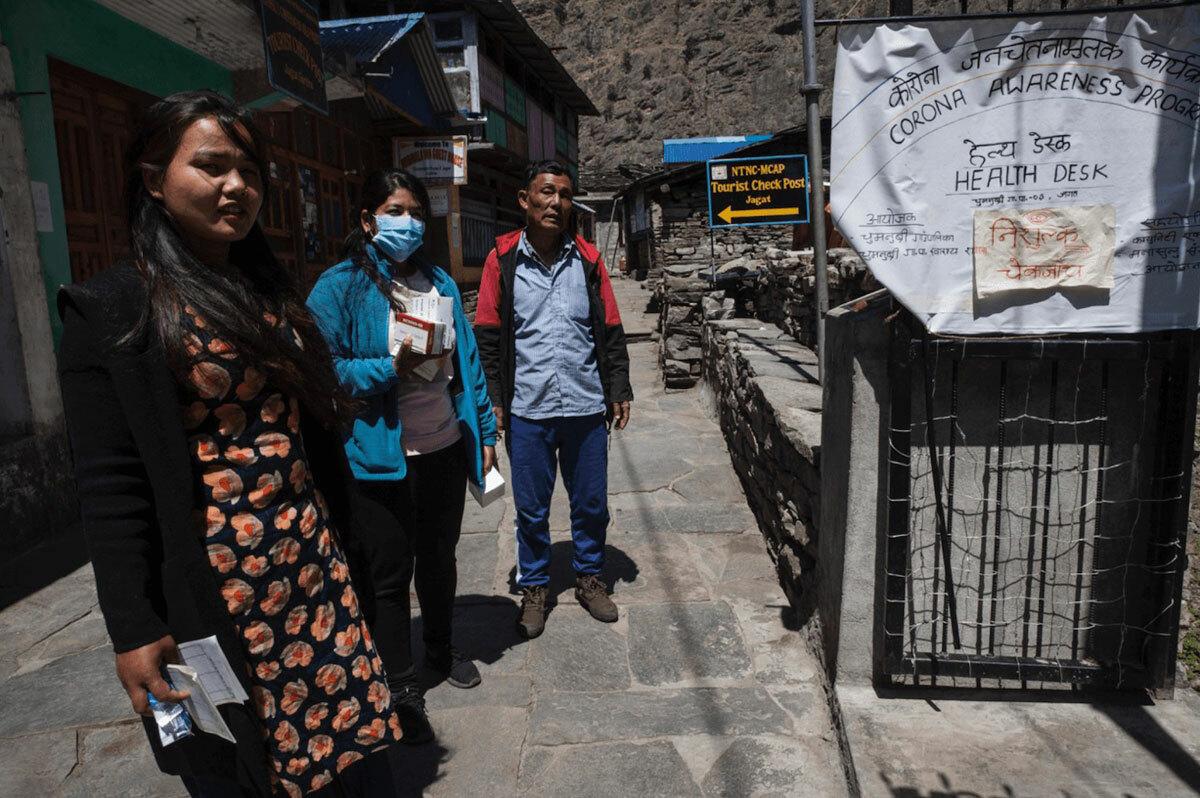 Du khách khi tới làng Jagat sẽ được đo thân nhiệt. Trong bản tin tivi cũng đưa về con số người chết trong dịch bệnh trên thế giới, như Italy và Mỹ. Ảnh: Nepal Times.