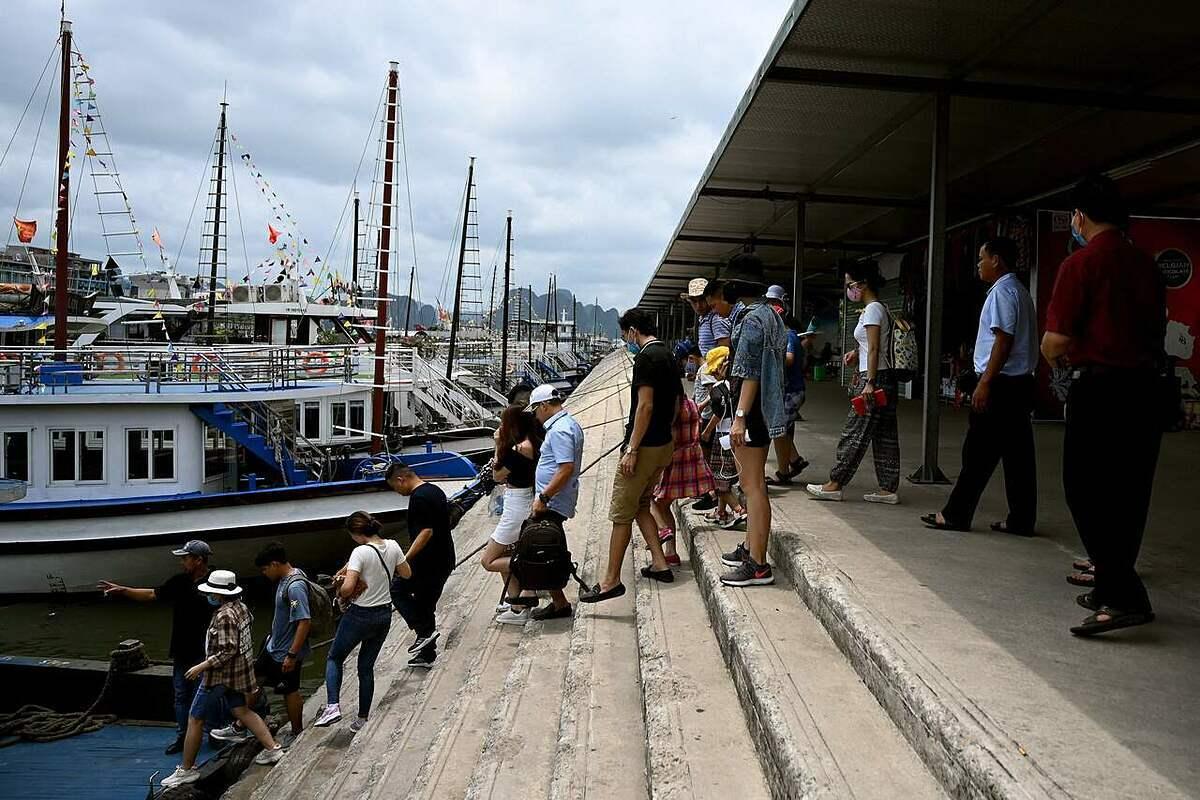 Du khách trong nước xếp hàng xuống thuyền tham quan vịnh Hạ Long vào giữa tháng 5, trong nỗ lực phục hồi du lịch của Việt Nam. Ảnh: AFP.