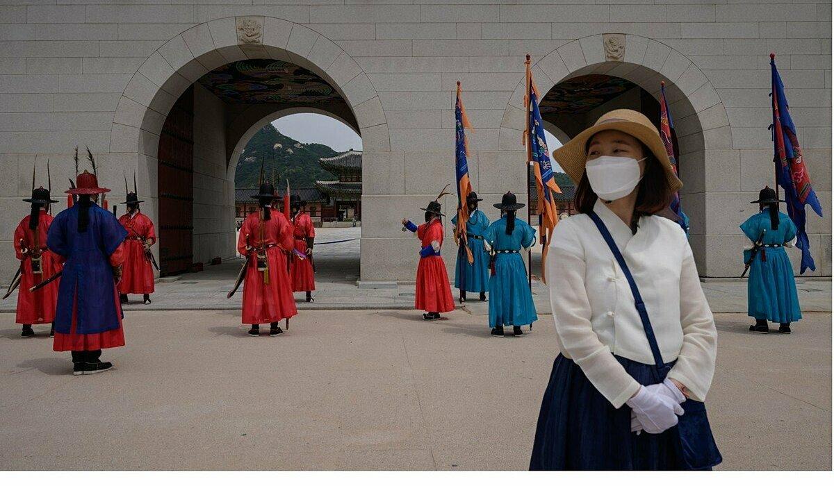 Du khách chụp ảnh trước cung điện Gyeongbokgung ở Seoul lúc đội bảo vệ đang thay ca trực. Hàn Quốc và Trung Quốc là một trong những quốc gia đầu tiên trên thế giới áp dụng bong bóng du lịch. Ảnh: AFP.