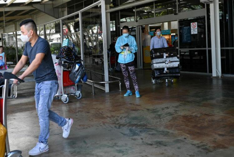 Hành khách đeo khẩu trang rời khỏi khu vực cửa đến của sân bay quốc tế Kingsford Smith vào buổi sáng ngày 21/3, sau khi Australia thực hiện lệnh cấm nhập cảnh đối với những người không phải công dân và không có thẻ xanh nhằm ngăn chặn sự lây lan của dịch bệnh tại Sydney. Ảnh: Reuters.