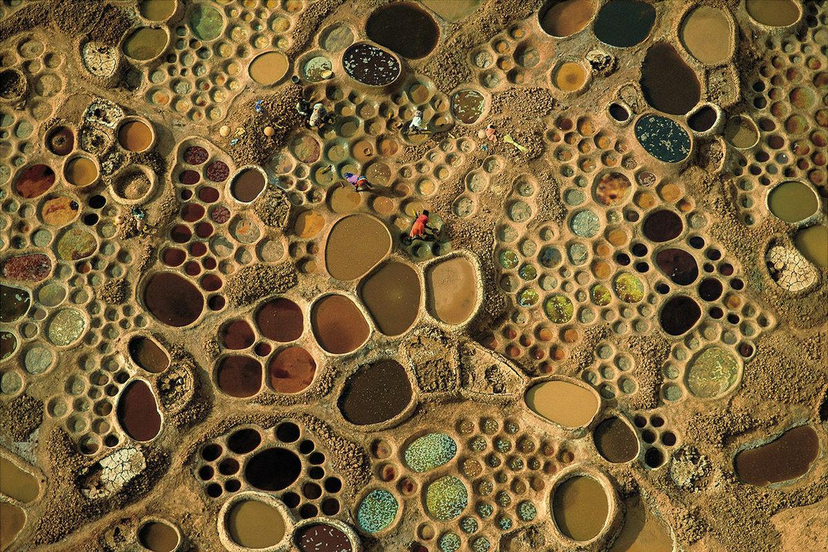Từ dù lượn của mình, George chụp được một bức tranh màu sắc tạo nên từ những hố cạn do người dân tự đào để lấy chất khoáng rắn cho gia súc. Màu sắc của từng hố phụ thuộc vào hỗn hợp bùn, tảo và muối. Teguidda-n-Tessoumt, Nigeria. Ảnh:George Steinmetz.