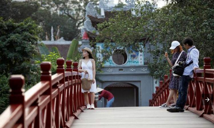 Du khách chụp ảnh bên cầu Thê Húc, Hồ Gươm, Hà Nội hôm 18/5. Ảnh: Kham/Reuters.