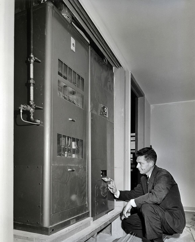 Một người quan sát hệ thống điều hòa tổng trong một căn nhà ở làng điều hòa. Ảnh: Dewey G. Mears/Austin Public Library.
