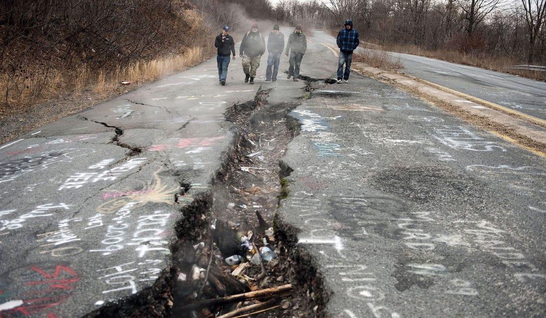 Khách du lịch khám phá vết nứt bốc khói trên cao tốc Graffiti, nơi từng là một phần của đường 61 vào năm 2010. Ảnh: AFP.