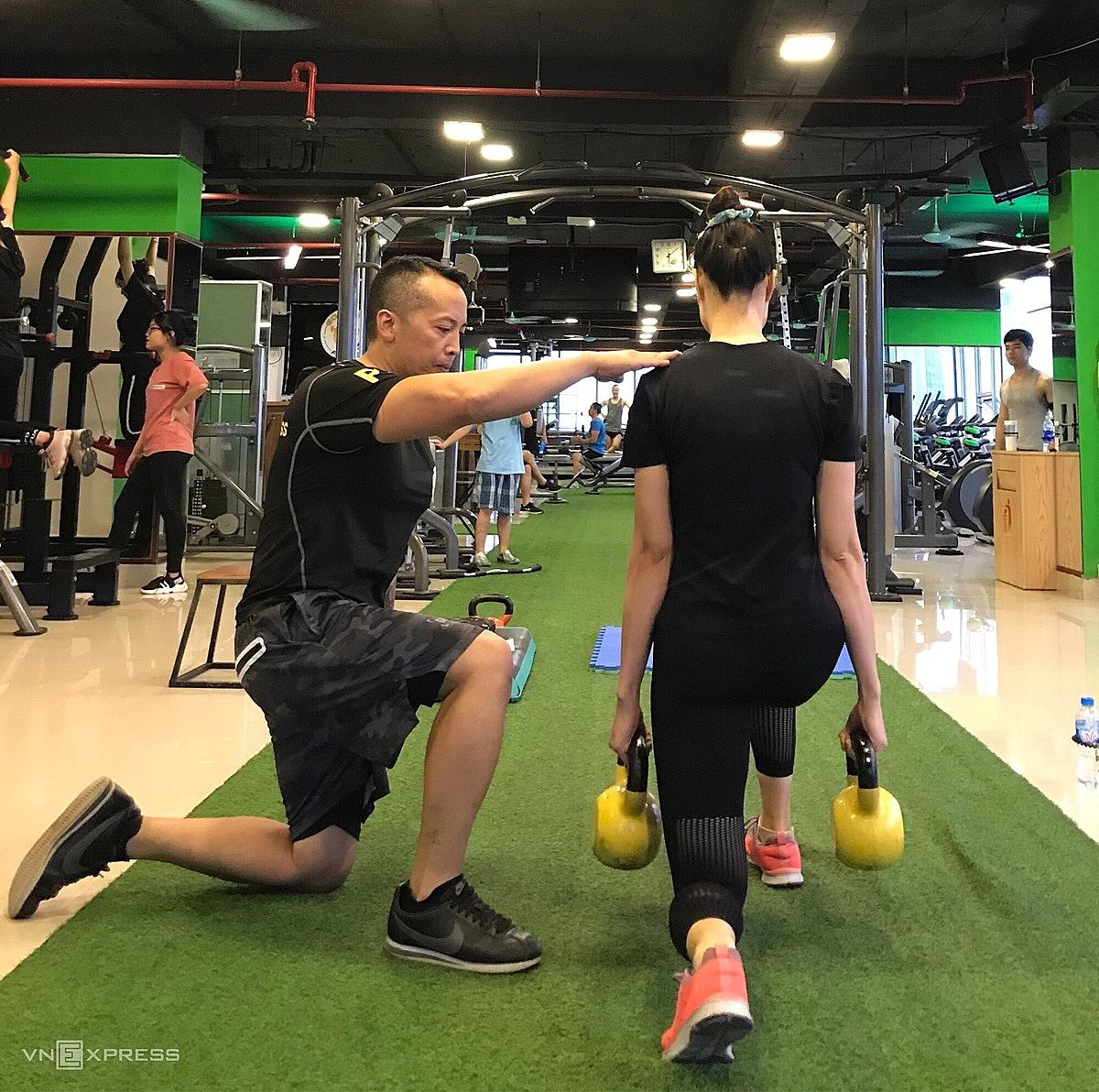 Trần Quang Anh (trái) hướng dẫn học viên tại một CLB Gym tại Tây Hồ, Hà Nội. Anh rất thích không gian trong phòng gym, bởi khi còn là hướng dẫn viên, phòng tập cũng là nơi anh hay lui tới để rèn luyện sức khỏe vào những mùa thấp điểm hay ngày nghỉ. Ảnh: NVCC.