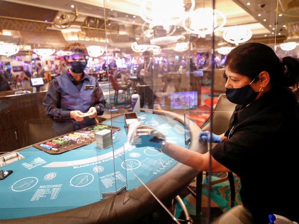 Sòng bạc Las Vegas, bang Nevada, Mỹ mở cửa trở lại vào 4/6 với các biện pháp an toàn như dựng tấm chắn mica giữa khách chơi và nhân viên phục vụ tại quầy chơi bài, quầy để nước rửa tay. Mọi người đều được yêu cầu đeo khẩu trang khi ngồi chơi tại chỗ. Cùng ngày, Eloina Marquez (áo đen) đang lau chùi các tấm chắn mica bảo vệ tại một bàn blackjack. Ảnh: Reuters