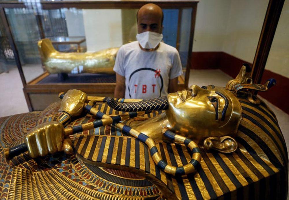 Các chuyến bay quốc tế được mở lại tới Ai Cập vào 1/7. Đồng thời, quốc gia này cũng mở cửa lại các điểm tham quan chính như Kim tự tháp Giza, bảo tàng Ai Cập... Du khách đến Kim Tự Tháp phải đeo khẩu trang và được đo thân nhiệt. Giới chức địa phương thông báo điểm tham quan này đã được làm sạch sâu hồi đầu năm, nhằm phòng tránh dịch bệnh. Trên ảnh, một du khách đang đứng trước quan tài của hoàng đế Tutankhamen trong Bảo tàng Ai Cập ở Cairo ngày đầu tiên của tháng 7. Ảnh: Mohamed Abd El Ghany/Reuters
