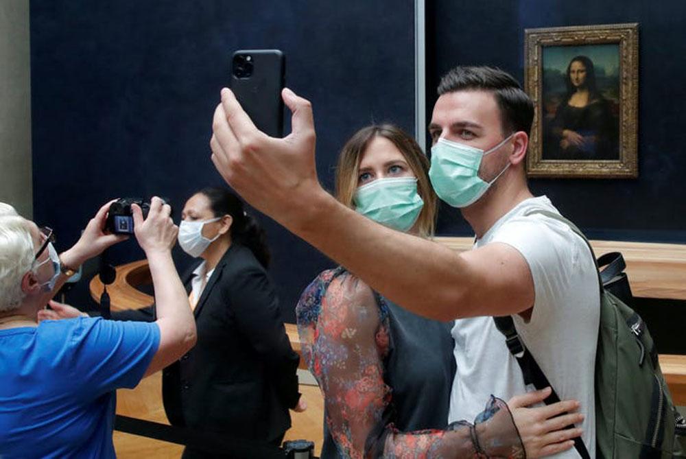 Hai du khách chụp ảnh trước bức tranh Mona Lisa nổi tiếng ở bảo tàng Louvre, Paris, Pháp vào 6/7. Khách muốn tới tham quan phải đeo khẩu trang, mua vé trực tuyến. Trên sàn nhà có đánh dấu vị trí từng người được đứng nhằm đảm bảo giãn cách an toàn giữa các du khách với nhau và khách chỉ có thể đi theo một chiều khi vào tham quan. Ảnh: Charles Platiau/Reuters