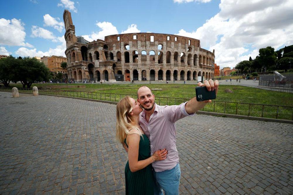 Cặp đôi người Đức chụp ảnh bên ngoài Đấu trường La Mã ở Rome, Italy vào 16/6. Từ 3/6, Italy trở thành quốc gia châu Âu đầu tiên mở cửa biên giới đón khách quốc tế, theo Afar. Đây cũng là đất nước chứng kiến một trong những đợt bùng phát Covid-19 mạnh mẽ nhất và đóng cửa biên giới lâu nhất trong châu lục. Ảnh: Guglielmo Mangiapane/Reuters