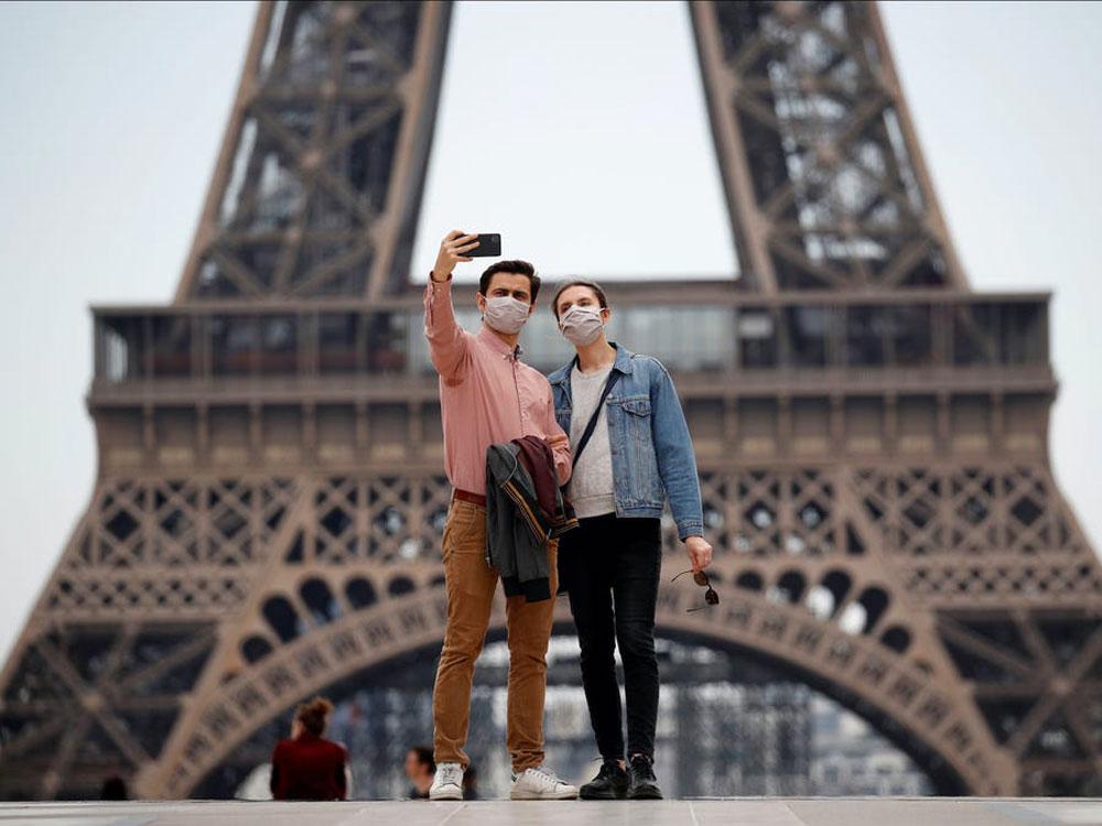 Du khách chụp ảnh tại quảng trường Trocadero gần tháp Eiffel, Paris, Pháp ngày 16/5. Khẩu trang, giãn cách xã hội và chấp hành một số lệnh cấm là những điều mà du khách đang dần làm quen khi đi chơi trong mùa dịch ở khắp thế giới. Tháp Eiffel mở cửa trở lại vào /25 6, sau ba tháng. Đây cũng là thời gian đóng cửa lâu nhất kể từ thế chiến thứ hai. Ảnh: Gonzalo Fuentes/Reuters