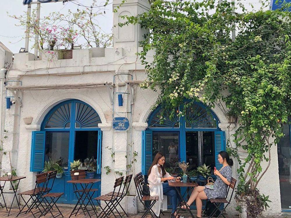 Santorini Vibes Cafe Quán cà phê nằm trên đường Nhật Chiêu lấy cảm hứng từ hòn đảo Santorini nổi tiếng ở Hy Lạp. Quán nổi bật trên nền trời xanh với ngôi nhà trắng, mái vòm xanh, điểm xuyết những tán hoa giấy hồng đỏ rực rỡ. Nội thất quán cũng mang hai màu trắng và xanh da trời, màu sắc đặc trưng của hòn đảo. Ngoài khung cảnh hồ Tây mát mẻ, du khách có thể check-in với những ô cửa hoặc chụp từ đường ven hồ để lấy trọn hình ảnh Santorini thu nhỏ. Giá đồ uống tại đây từ 35.000 - 50.000 đồng. Ảnh: Santorini Vibes Cafe