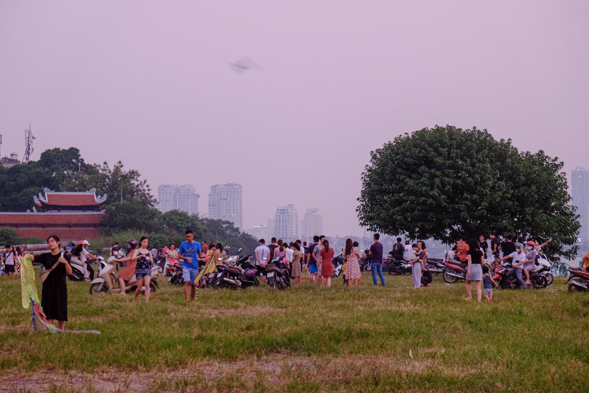 Tuy nhiên, chiều đến trời dịu mát hơn, các tuyến đường quanh Hồ Tây như Thanh Niên, Quảng Khánh, Quảng Bá... tập trung rất đông người. Trên hình là khu vực bãi cỏ sau Phủ Tây Hồ, thu hút hàng trăm người đến vui chơi, thả diều, dã ngoại hoặc tổ chức chèo SUP ở hồ.Theo đại diện công viên nước Hồ Tây, ước tính năm nay có 2.000 khách đến công viên dù đã kéo dài thời gian mở cửa, trong khi cùng thời điểm này năm ngoái có 10.000 khách. Ảnh: Hương Chi
