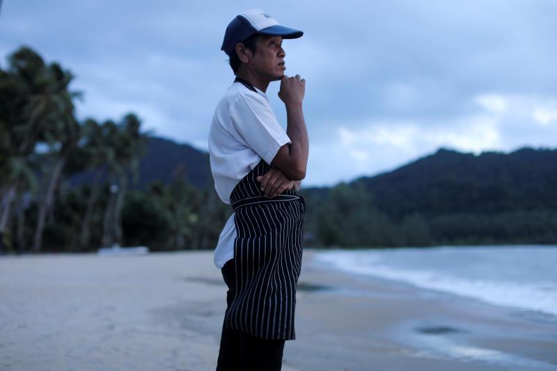 Một đầu bếp đứng nhìn bãi biển vắng bóng khách du lịch trên đảo Koh Chang hồi cuối tháng 7. Anh mong đợi du khách sớm quay lại như những ngày xa xưa ấy. Ảnh: Reuters
