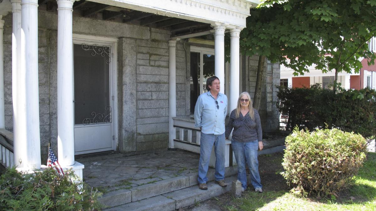 Cùng đứng trước cửa nhà, Brian Dumoulin lại ở đất Mỹ, còn vợ ông - bà Joan, đứng trên đất Canada.  Giữa họ là một cột mốc nhỏ. Ảnh: AP