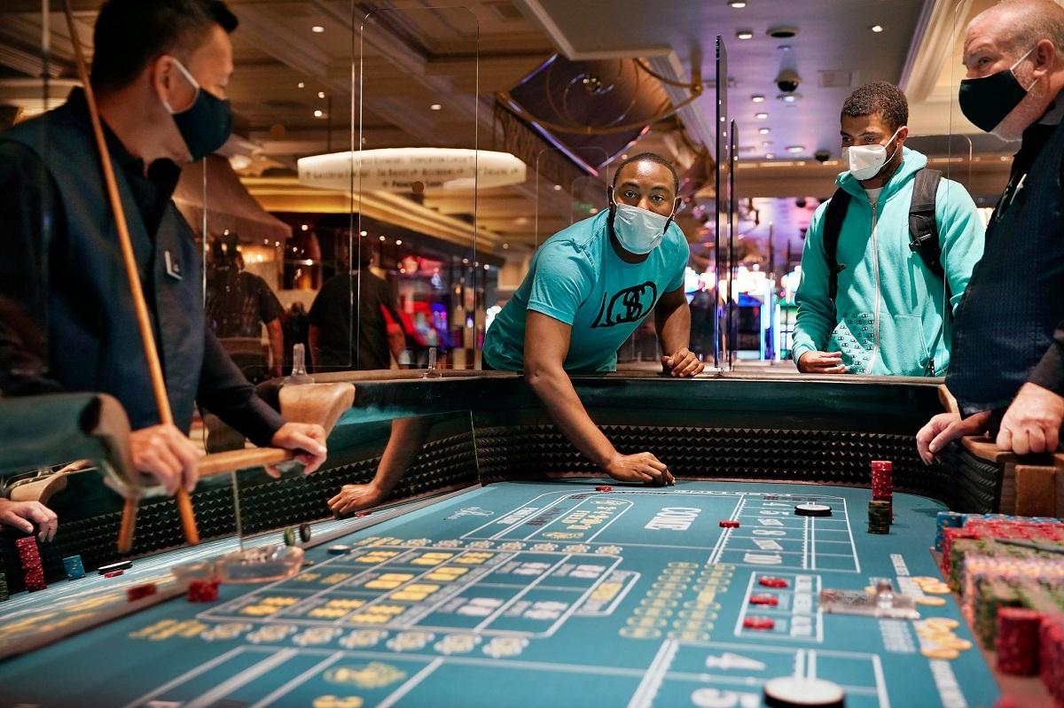 Khách đặt cược trên một bàn lắp màn chắn trong khách sạn sòng bài Bellagio, Las Vegas. Ảnh: AP