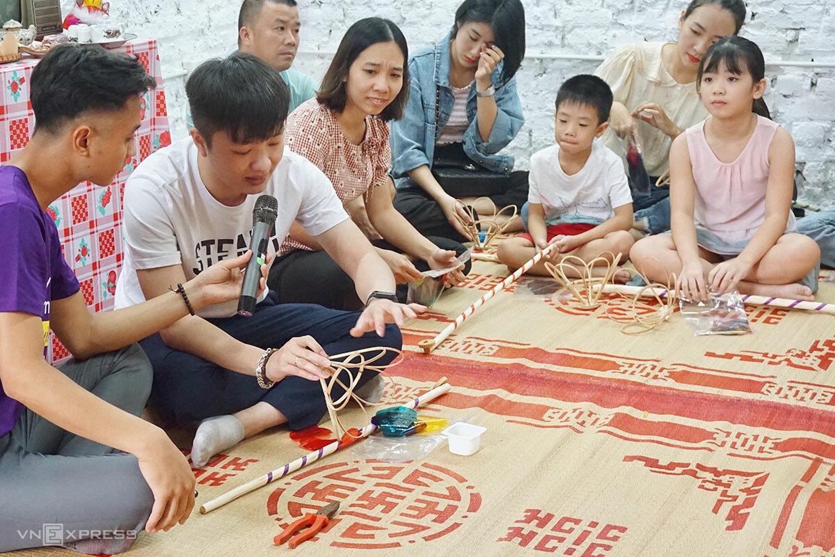 Anh Hữu Thăng (áo trắng) hướng dẫn các công đoạn làm đèn cù trong sự kiện trung thu của Tổ chức Tình nguyện vì giáo dục (VEO). Ảnh: Ngân Dương