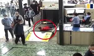 Chui vào máy quét hành lý để không phải xếp hàng