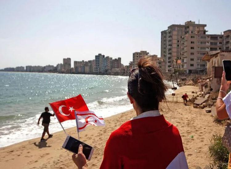 Một người phụ nữ cầm cờ của Thổ Nhĩ Kỳ và Cộng hòa bắc Cyprus thuộc Thổ Nhĩ Kỳ tự xưng khi du khách được quay lại Varosha. Ảnh: AFP