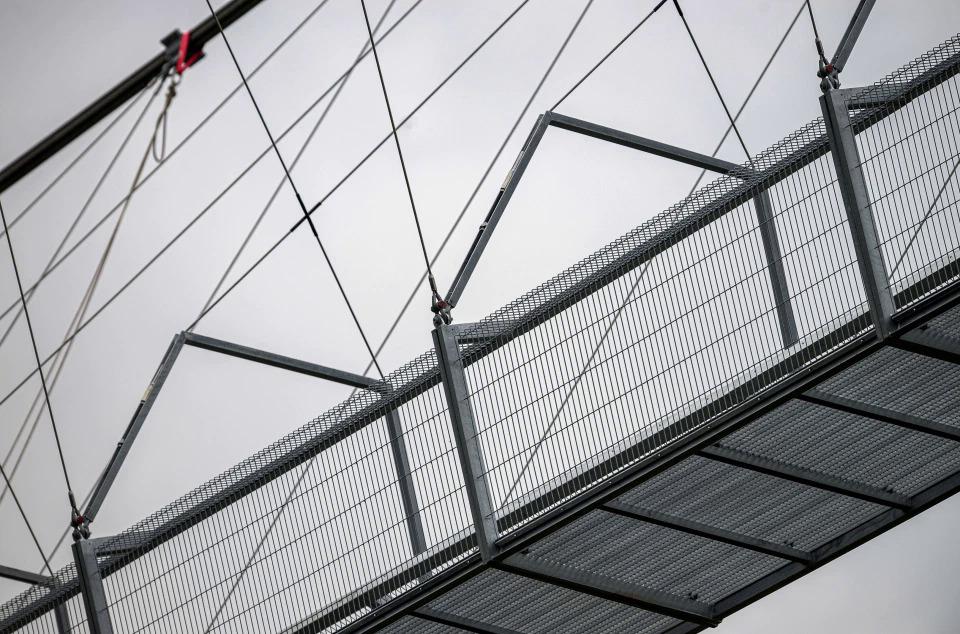 Được xây dựng từ hệ thống cáp và lưới bằng kim loại, cầu kết nối hai đầu là 2 tháp hình chữ V ngược với đáy kín, không dùng kính trong. Du khách tốn khoảng  5 - 10 phút để đi bộ hết cầu hoặc lâu hơn chút nữa nếu muốn dừng lại ngắm cảnh từ trên cầu.