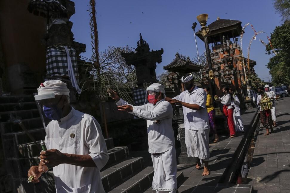 Người dân Bali theo đạo Hindu đeo khẩu trang trong ngày lễ Saraswati Day vào 4/7. Ảnh: AFP